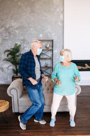 Photo pour Les conjoints âgés portant des masques médicaux protecteurs passent du temps libre en quarantaine et dansent à la maison. mari aîné et femme aînée dansent dans le salon - image libre de droit