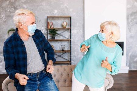 Photo pour Un couple de personnes âgées positif et joyeux portant des masques de médecine s'amuse à la maison pendant la quarantaine. Les conjoints âgés dansent avec des masques chirurgicaux sur le visage - image libre de droit