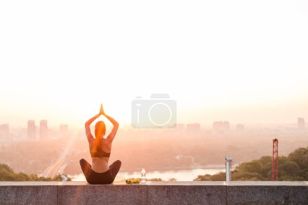 Balance with nature and the city. Rear view of young beautiful fit woman in sportswear doing yoga while sitting against industrial city view