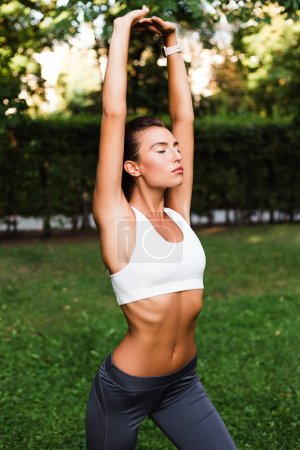 Calm yoga. Young beautiful fit woman in sportswear doing yoga in green park