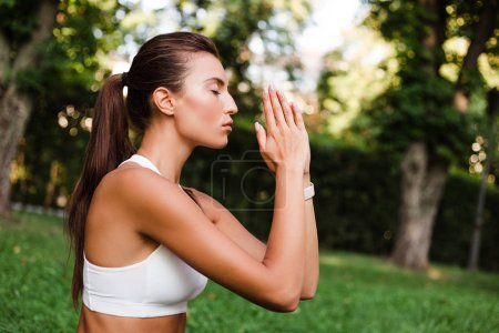 Trust in yoga. Young beautiful fit woman in sportswear doing yoga in green park