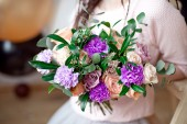 Close-up view of teen girl with dreadlocks hairstyle holding a bouquet of flowers indoors