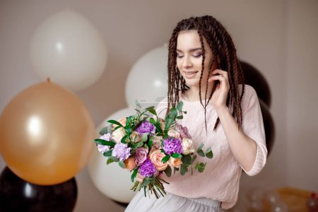 Smiling teenage girl with dreadlocks hairstyle holding a bouquet of flowers in hands indoors.