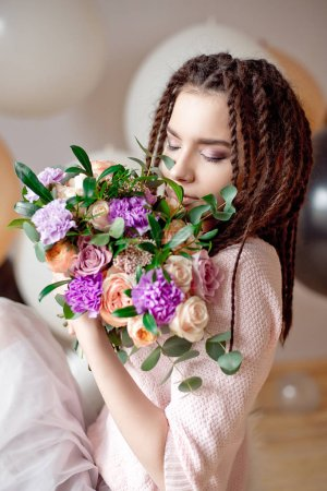 Beautiful woman with dreadlocks hairstyle holding a bouquet of flowers in hands indoors.