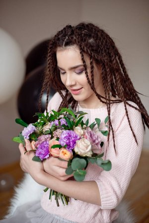 beautiful teen girl with dreadlocks hairstyle holding a bouquet of flowers indoors