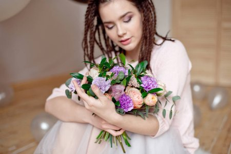 Smiling girl with dreadlocks hairstyle showing a bouquet of flowers in hands indoors. Focus on flowers with blurred girl  on background.