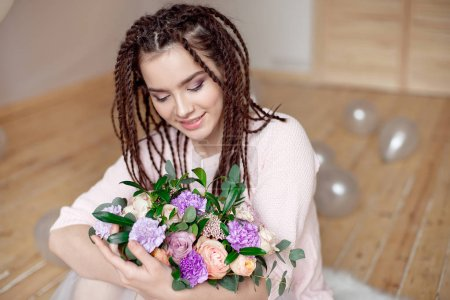 Close up view of beautiful teen girl with dreadlocks hairstyle holding a bouquet of flowers indoors