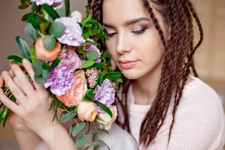 Close-up portrait of beautiful teen girl with dreadlocks hairstyle holding a bouquet of flowers indoors