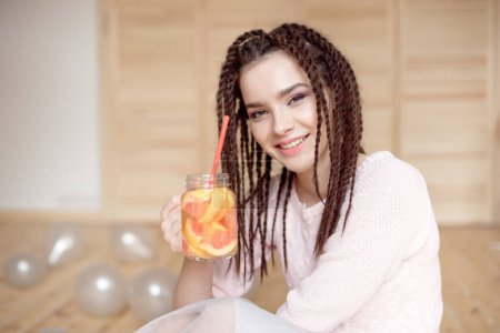 Young smiling woman holding mason jar with lemonade indoors.