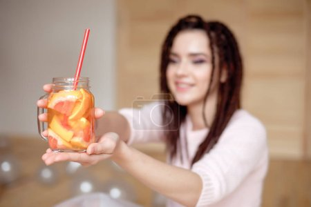 Young pretty woman blurred on background holding mason jar with lemonade indoors.