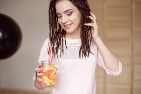 Young pretty girl holding mason jar with lemonade indoors.