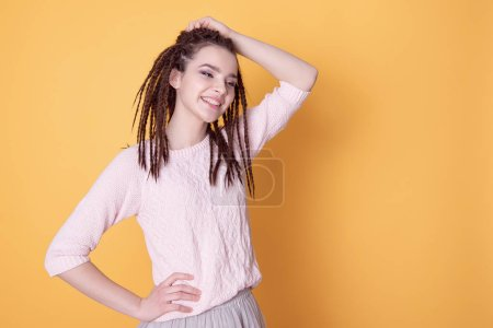 Close up portrait of smiling woman with dreadlocks hairstyle.