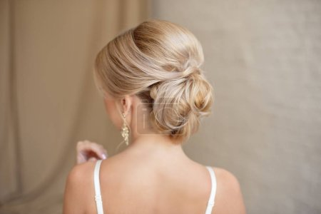 Rear view of female hairstyle middle bun with blond hair