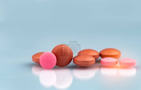 Selective focus on orange and pink round tablets with shadow on gradient background. Pharmaceutical industry. Pharmacy products. Vitamins and supplements concept. Tablets pills texture background.
