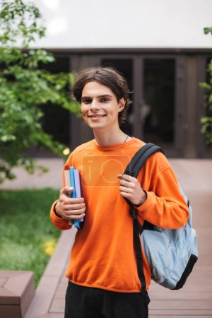 Smiling boy standing with backpack and books in hand and happily looking in camera in courtyard of university