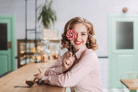 Young beautiful lady sitting at the bar counter and covering her eye with lollipop candy while happily looking in camera in cafe