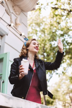 Young smiling lady in leather jacket standing with milkshake in hand and happily looking aside while waving to someone