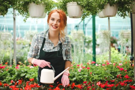 Young beautiful florist in apron standing with watering can and happily looking in camera while working in greenhouse