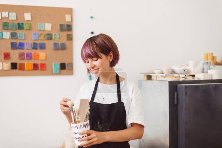 Smiling girl with colorful hair in black apron and white T-shirt holding bowl with pottery tools in hand happily spending time at pottery studio