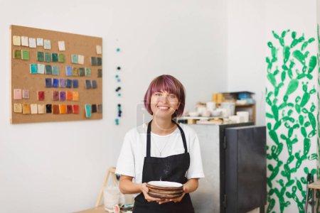 Photo pour Jolie fille souriante en tablier noir et T-shirt blanc tenant des assiettes faites à la main dans les mains regardant joyeusement à la caméra au studio de poterie - image libre de droit