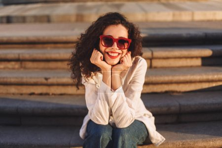 Young beautiful lady with dark curly hair in sunglasses and white jacket sitting on stairs on street and happily looking in camera