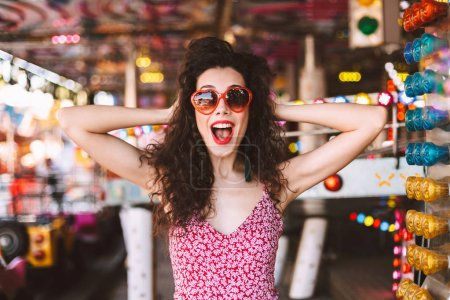 Young joyful lady with dark curly hair in sunglasses and dress happily looking in camera while standing in amusement park with attractions on background