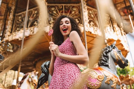 Young joyful lady with dark curly hair in dress standing with lolly pop candy in hands and happily looking in camera with beautiful carousel on background