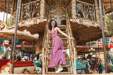 Beautiful smiling lady with dark curly hair in sunglasses and dress standing with lolly pop candy in hand and happily looking aside while spending time on carousel