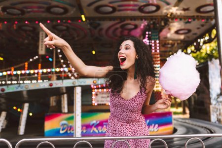 Young joyfull woman with dark curly hair in dress standing with cotton candy in hand and happily showing index finger aside while spending time in amusement park with attractions on background