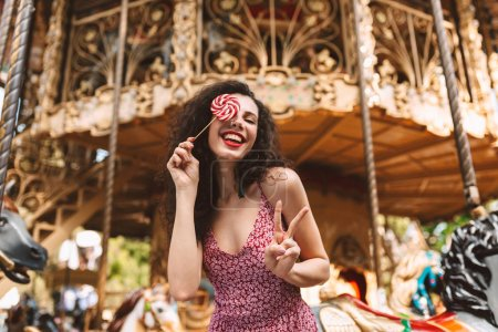 Joyful lady with dark curly hair in dress standing and covering her eye with lolly pop candy while happily looking in camera with beautiful carousel on background