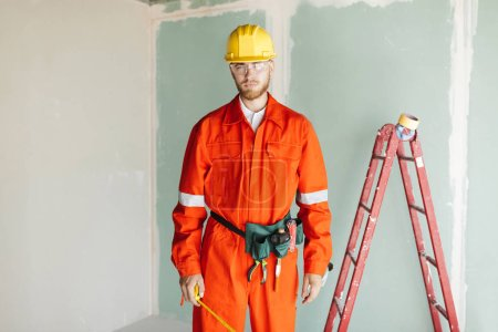 Young builder in orange work clothes and yellow hardhat holding roulette in hand thoughtfully looking in camera with ladder on background