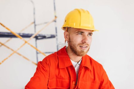 Portrait of young foreman in orange work clothes and yellow hardhat with pencil behind ear thoughtfully looking aside with scaffolding on background