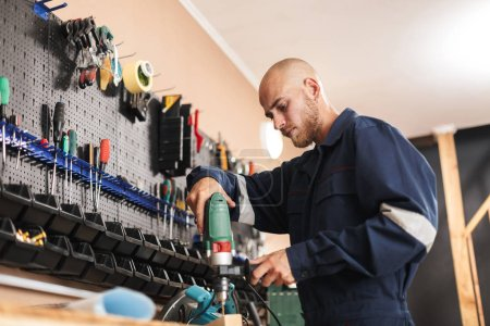 Young foreman in work clothes thoughtfully using electric drill with stand of tools near in workshop