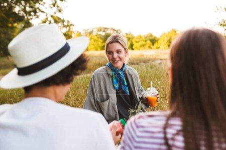 Photo pour Belle fille souriante tenant du jus dans la main parlant joyeusement avec des amis passer du temps sur le pique-nique dans le parc - image libre de droit