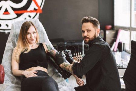 Photo pour Tatoué, fille et tatoueur professionnel heureusement cherche à huis clos alors que faire tatouage sur place de machine de tatouage en studio - image libre de droit