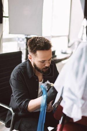 Professional tattoo master thoughtfully doing tattoo using tattoo machine in modern studio
