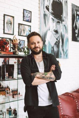 Photo pour Maître de tatouage souriant debout avec les mains jointes regardant joyeusement dans la caméra passer du temps dans un studio de tatouage moderne - image libre de droit