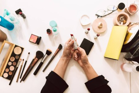Close up make up artist holding red lipstick in hands with variety of cosmetic products on desk isolated