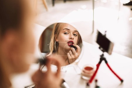 Young pretty girl looking in little mirror on table using red lipstick recording new video for vlog