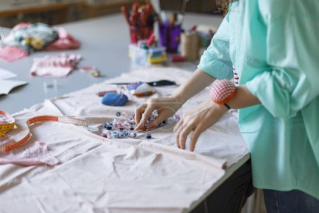 Close up tailor in shirt choosing colorful thread working with fabric in modern sewing workshop