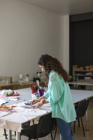 Young seamstress in shirt choosing colorful thread for work with fabric in modern sewing workshop