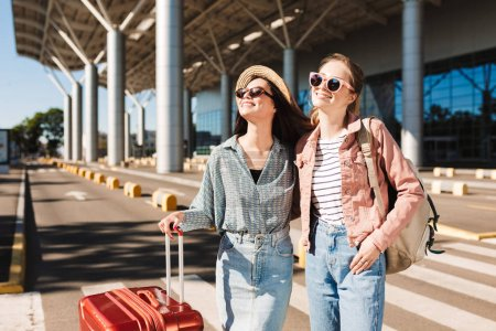 Photo for Two pretty smiling girls in sunglasses joyfully looking aside with red suitcase and backpack outdoor near airport - Royalty Free Image
