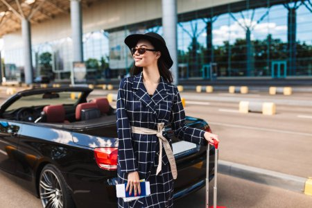Beautiful smiling girl in sunglasses and black hat holding passport with flight ticket joyfully looking aside near airport with cabriolet car on background