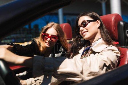 Photo pour Jolie fille souriante en lunettes de soleil regardant joyeusement de côté conduisant une voiture cabriolet avec une amie proche sur les rues de la ville en plein air - image libre de droit