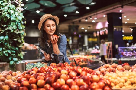 Photo for Pretty smiling girl in hat dreamily choosing peaches in modern supermarket - Royalty Free Image