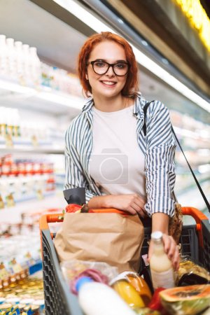Pretty smiling girl in eyeglasses and striped shirt with shopping cart full of products happily looking in camera in dairy department of modern supermarket