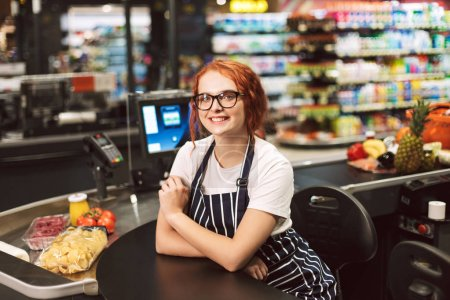 Pretty smiling cashier in eyeglasses and striped apron happily looking in camera working in modern supermarket