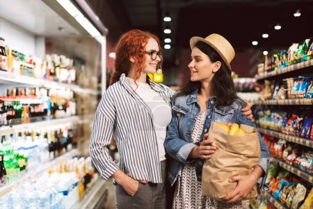 Cheerful girls with paper grocery  bag full of products joyfully looking at each other spending time in modern supermarket