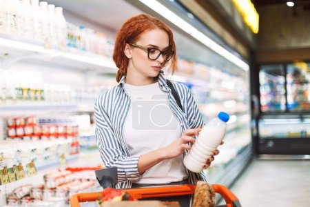 Young woman in eyeglasses and striped shirt with shopping cart thoughtfully looking on bottle of milk in modern supermarket