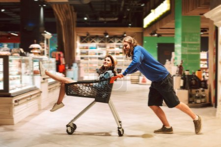 Young guy pushing shopping trolley with pretty girl inside happily spending time together in modern supermarket